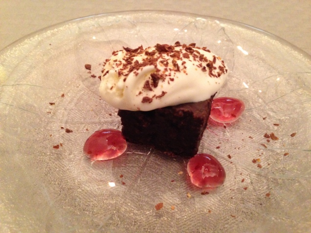 Chocolate brownie with vanilla ice cream and raspberry sauce.